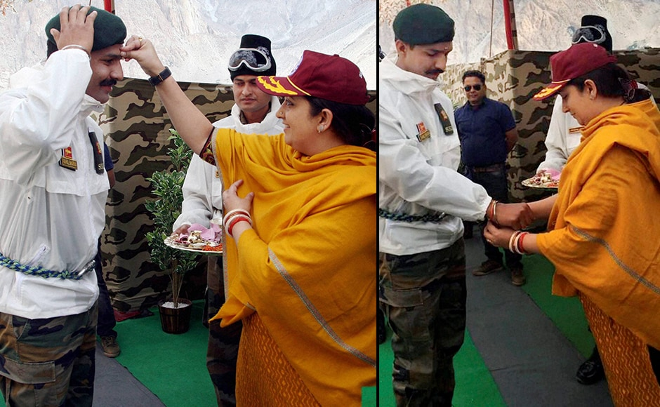 "Textiles Minister Smriti Zubin Irani puts a tilak & tying Rakhi to a soldier as she celebrates ""Raksha Bhandan"" with Army jawans at Siachen base camp on Thursday. PTI Photo / PIB (PTI8_18_2016_000343B)"