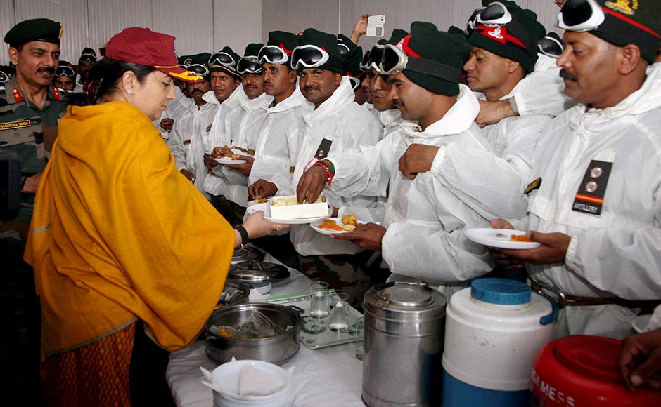 "Textiles Minister Smriti Zubin Irani distributing sweets to Army jawans while celebrating ""Raksha Bhandan"" with them at Siachen base camp on Thursday. PTI Photo / PIB (PTI8_18_2016_000344B)"