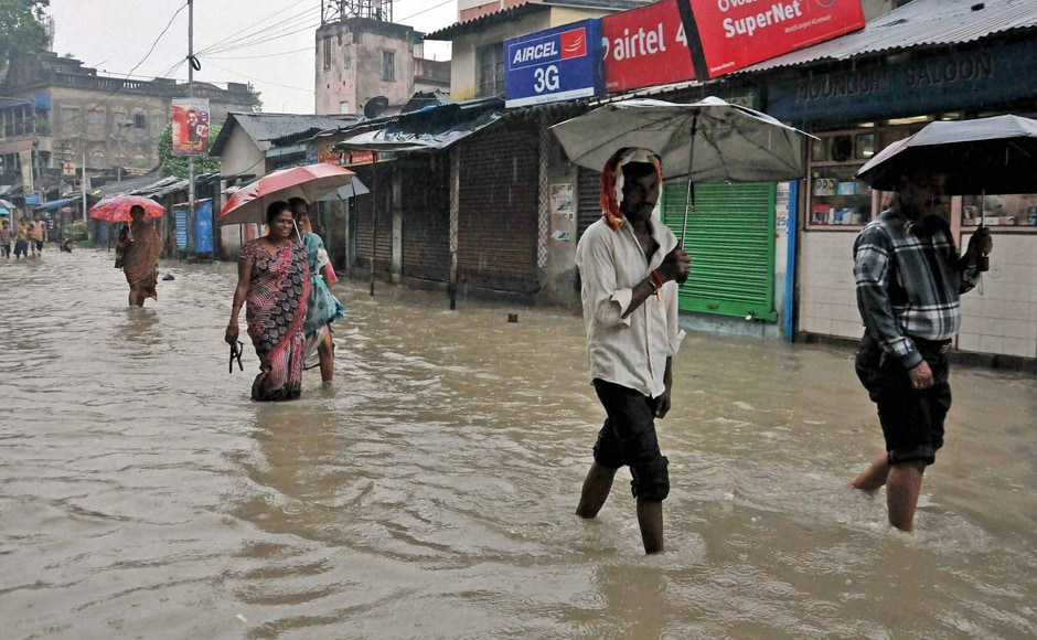 West Bengal is on high alert after a deep depression near the coastal town of Digha has brought heavy rainfall in all southern districts of the state. People have to move through water logged road at Kalighat Kali temple area in Kolkata on Sunday. Photo: PTI