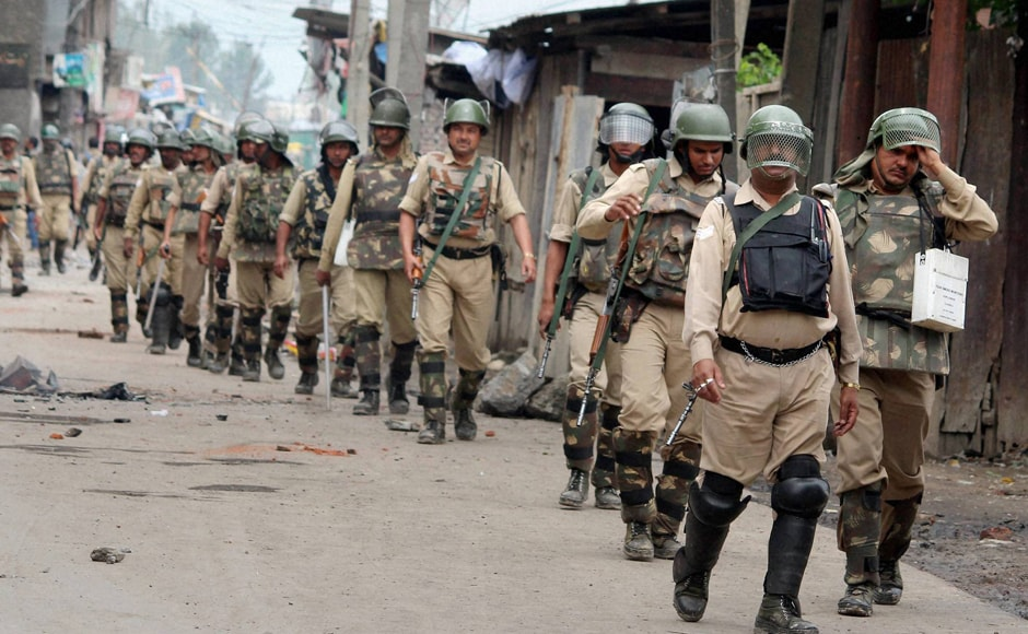Security personnel patrol a deserted street after curfew was imposed following fresh clashes, at Batamallo in Srinagar. Clashes were reported from a number of places in Srinagar city but nobody was hurt in these incidents. PTI