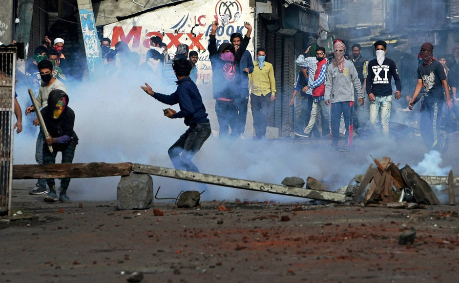 Protesters throw stones on security forces amid heavy tear smoke during a clash in Srinagar. The security forces used tear gas to chase the protesters but no one was hurt in these incidents. PTI