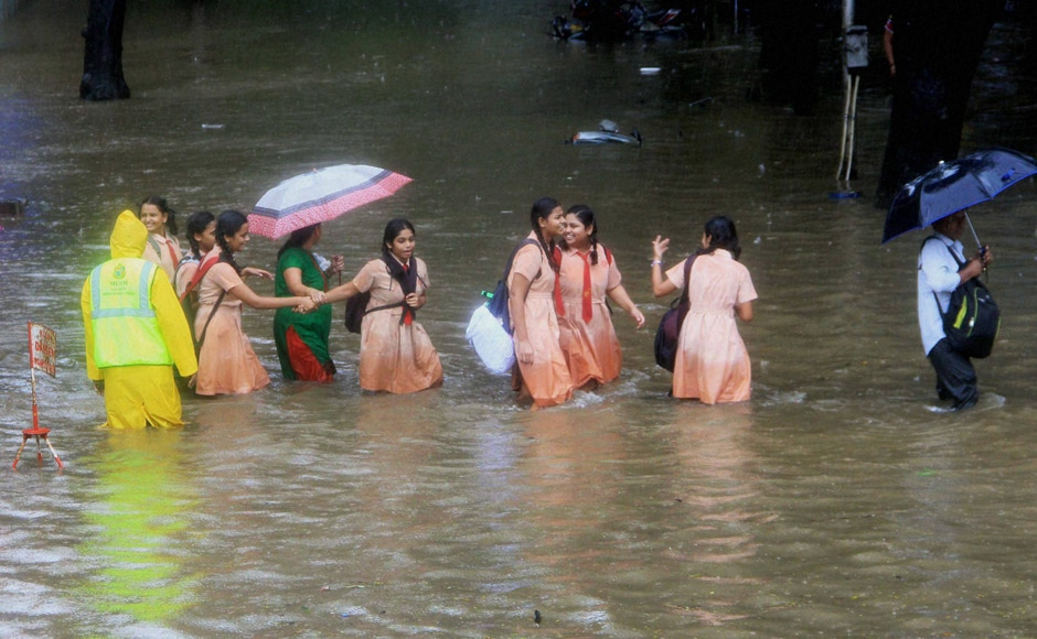 School children wading through flooded street during heavy rains in Mumbai on Friday. Besides Mumbai, the adjoining districts of Thane, Palghar and Raigad were also lashed by heavy rains, slowing traffic on all major routes linking Mumbai to Ahmedabad, Pune, Nashik and Goa. PTI