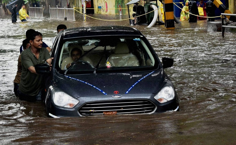 People pushing car through flooded street during heavy rains in Mumbai on Friday. Potholes and heavy waterlogging became a major nuisance for people. PTI