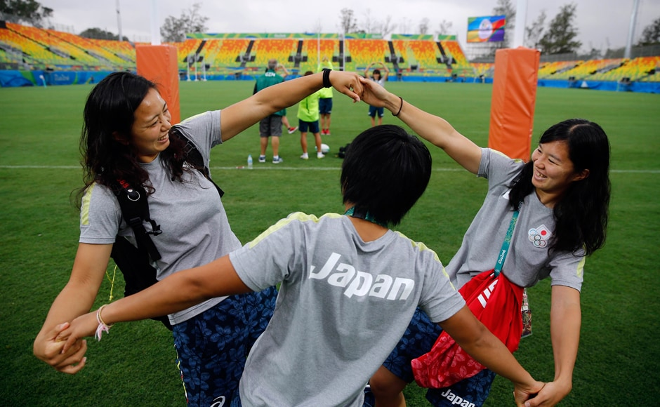 Japan's women's rugby sevens team share a light moment as they arrive for their practice session. Reuters