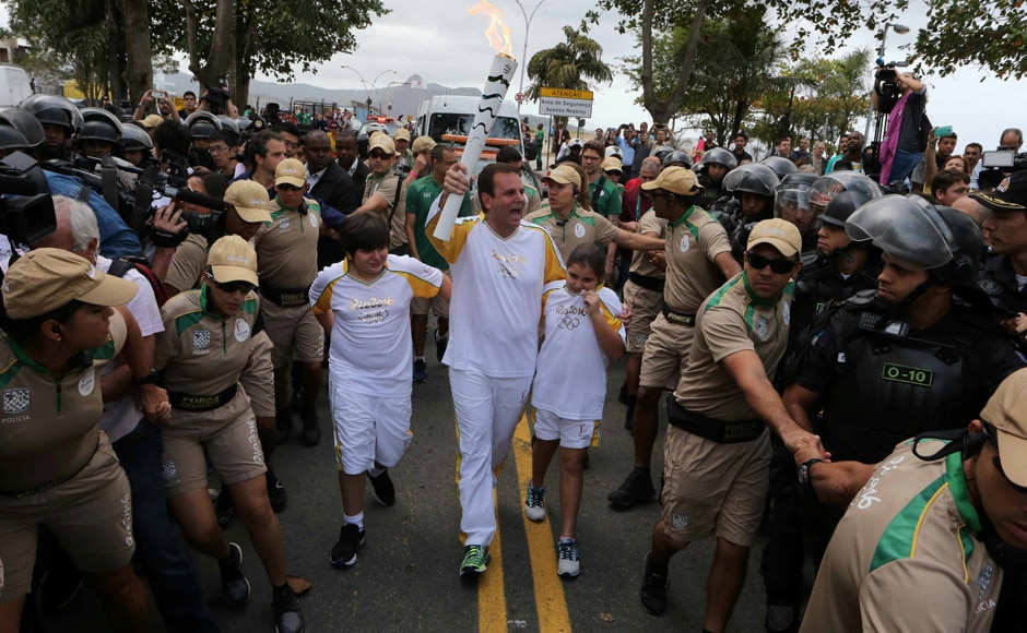 Rio de Janeiro' mayor Eduardo Paes carries the Olympic torch just after it was transported across the Guanabara Bay from Niteroi to Rio de Janeiro. Reuters