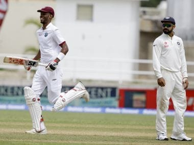 Roston Chase bats his way to a century as Virat Kohli looks on. AP