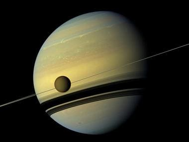Titan, Saturn's largest moon appears before the planet. Reuters
