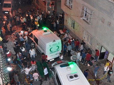 """People carry dead bodies into ambulances after an explosion in Gaziantep, southeastern Turkey, early Sunday, Aug. 21, 2016. A bomb attack targeting an outdoor wedding party in southeastern Turkey killed several people and wounded dozens. Deputy Prime Minister Mehmet Simsek said the """"barbaric"""" attack in Gaziantep, near the border with Syria, on Saturday appeared to be a suicide bombing. (DHA via AP)"""