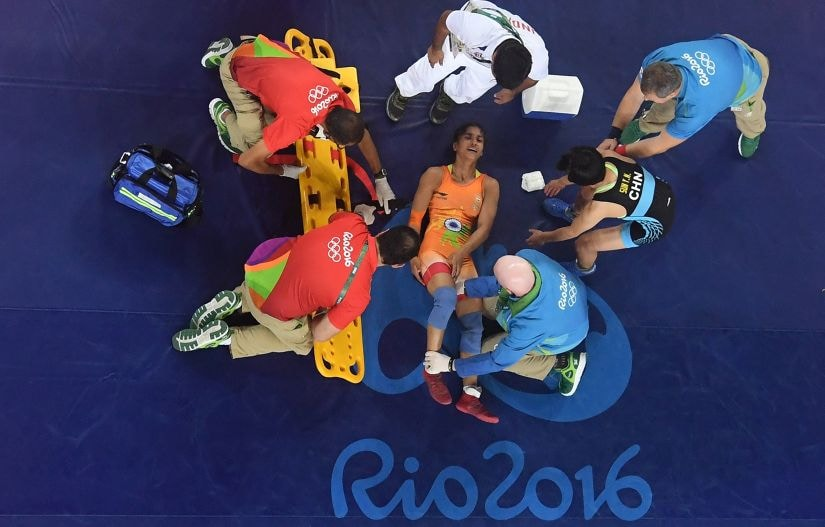 Injured Vinesh Vinesh is treated during a Women's Freestyle 48kg Quarterfinal bout. Getty Images