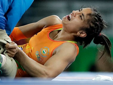 India's Vinesh Phogat in tremendous as she is attended to by a doctor after getting injured in her match against China's Sun Yanan. AP