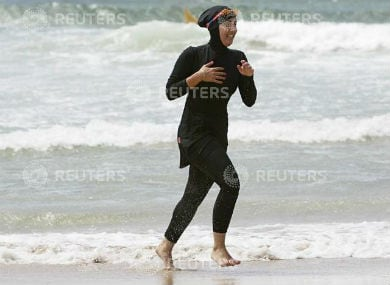 """Twenty-year-old trainee volunteer surf life saver Mecca Laalaa runs along North Cronulla Beach in Sydney during her Bronze medallion competency test January 13, 2007. Specifically designed for Muslim women, Laalaa's body-covering swimming costume has been named the """"burkini"""" by its Sydney based designer Aheda Zanetti. REUTERS"""