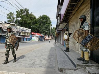 Security jawans stand guard as tension prevails in Srinagar. PTI
