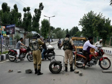 Police stands guard as curfew continues in several districts of Kashmir. PTI