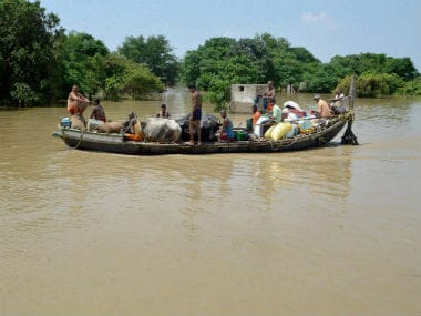 Villagers navigate through flooded waters in Patna. PTI.