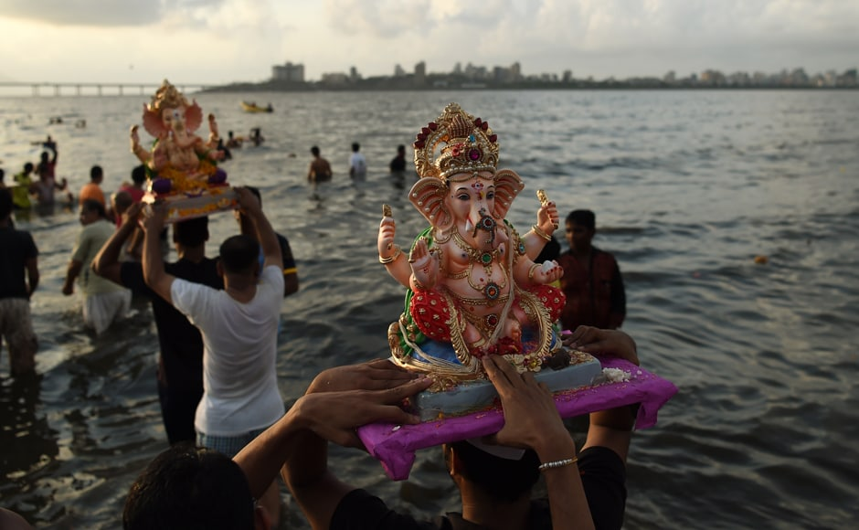 Devotees carry idols of Ganesh for immersion at the Dadar Chowpatty beach on the sixth day of the eleven-day long festival Ganesh Chaturthi in Mumbai on Saturday. (Photo courtesy: AFP)