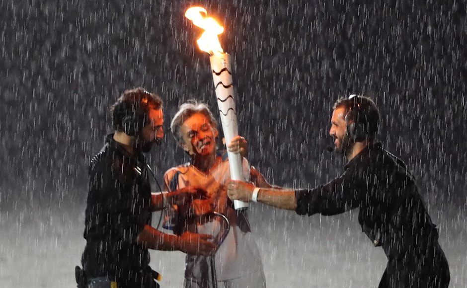 Brazilian Paralympic runner Marcia Malsar is assisted after falling while carrying the torch as rain falls during the opening ceremony. Reuters