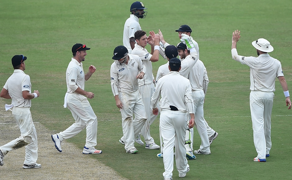 New Zealand's Mitchell Santner celebrates the wicket of Cheteshwar Pujara with teammates. AFP