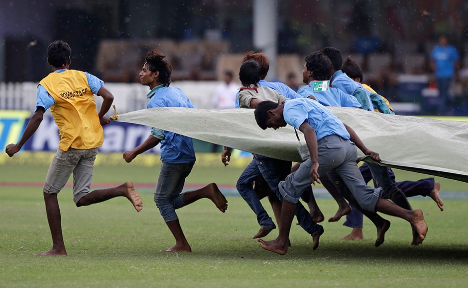 Ground officials cover the cricket pitch as it rains on the second day of the test cricket match between New Zealand and India in Kanpur, India, Friday, Sept. 23, 2016. (AP Photo/ Tsering Topgyal)