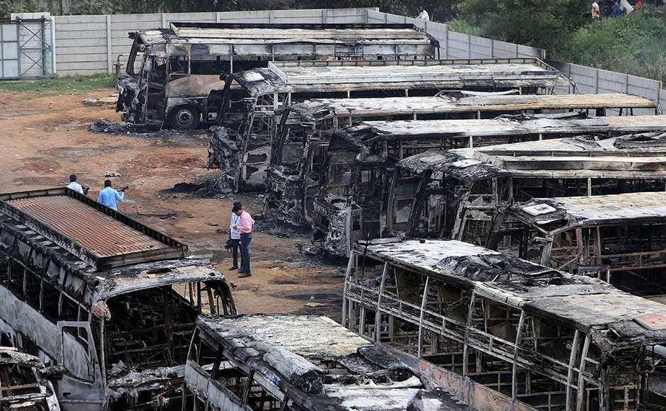 Charred remains of passenger buses, owned by a transport company from the neighboring Tamil Nadu state, lie in a yard a day after they were set ablaze by angry mobs in Bengaluru on Monday. (Photo: AP)