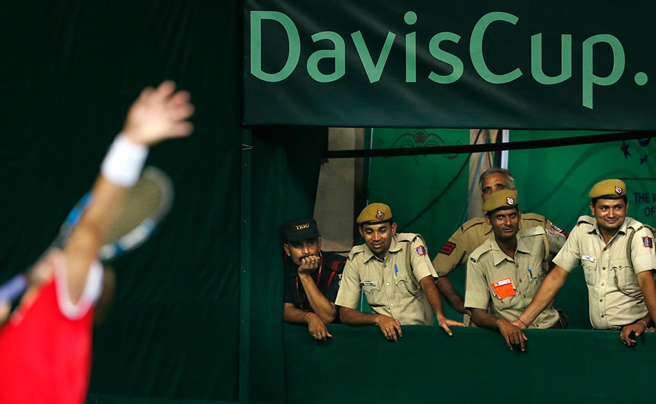 Indian policemen watch a Davis Cup men's tie tennis match between Spain's David Ferrer, left, and India's Saketh Myneni in New Delhi, India, Friday, Sept. 16, 2016. (AP Photo/Saurabh Das)