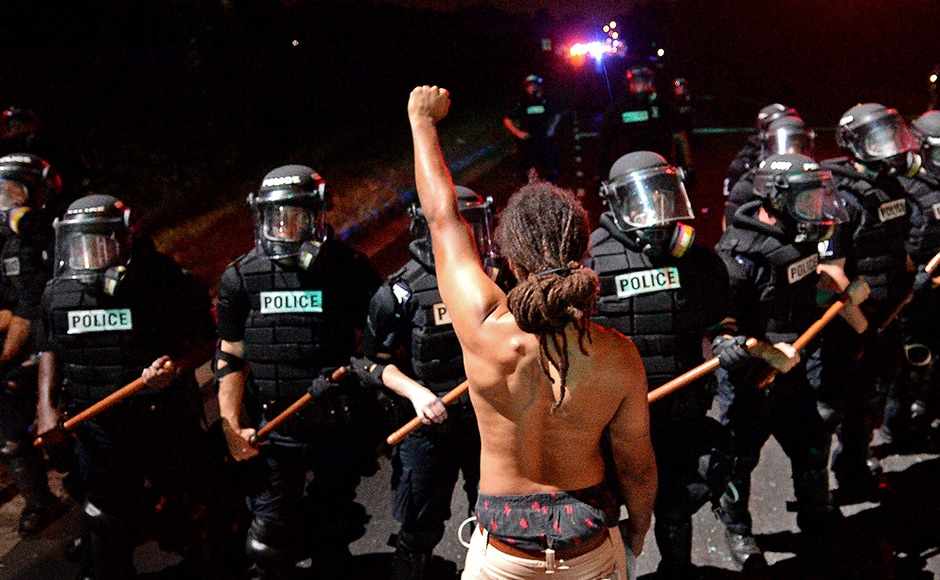 A protester stands with his left arm extended and fist clenched in front of a line of police officers in Charlotte, North Carolina on Tuesday. Protesters blocked a highway and clashed with police after officers fatally shot a black man they said had a gun when they approached him in a parking lot. AP