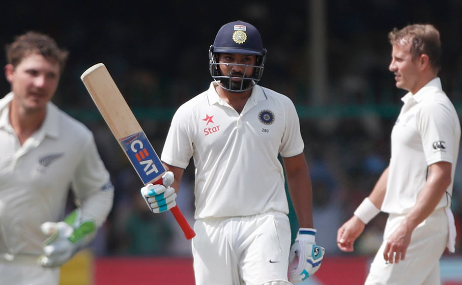 India's Rohit Sharma raises bats after scoring fifty runs. He batted positively with the strike rate of 73. AP