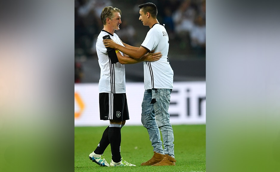 Germany's Bastian Schweinsteiger talks to a fan who jumped on the pitch during the match in Moenchengladbach. AP