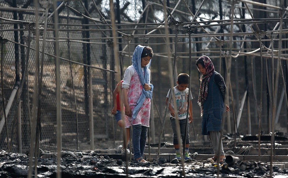 Migrants stand among the remains of a burned tent at the Moria migrant camp. At least nine people were arrested on accusations of damaging property and causing unrest and were expected to appear before a prosecutor, a police official in Athens said. Reuters
