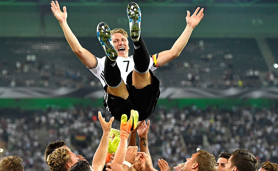 Germany's national team throws their captain Bastian Schweinsteiger into the air after he played his last match for the national team in Moenchengladbach, Germany, Wednesday, Aug. 31, 2016. Germany won the friendly soccer match against Finland with 2-0.AP