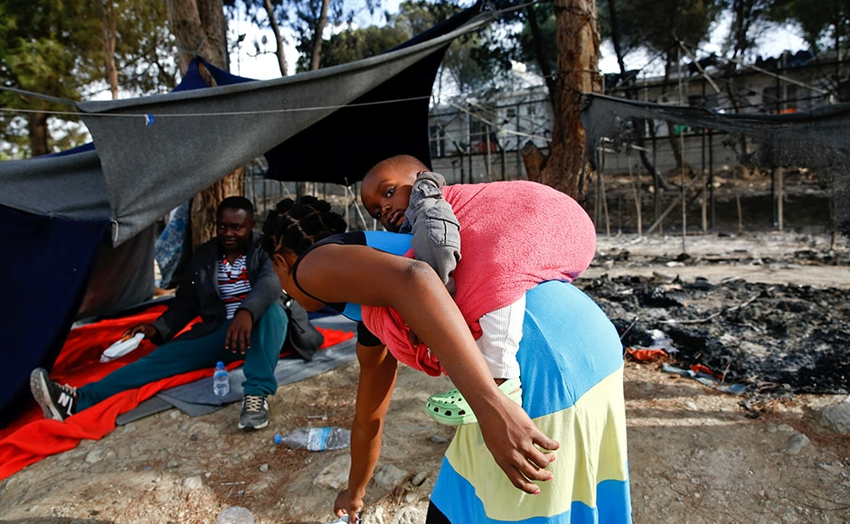 A migrant woman carries a baby as she stands next to the remains of a burned tent at the Moria migrant camp. Tensions have boiled over at overcrowded camps on Greece's islands as the slow processing of asylum requests adds to frustration over living conditions. Reuters