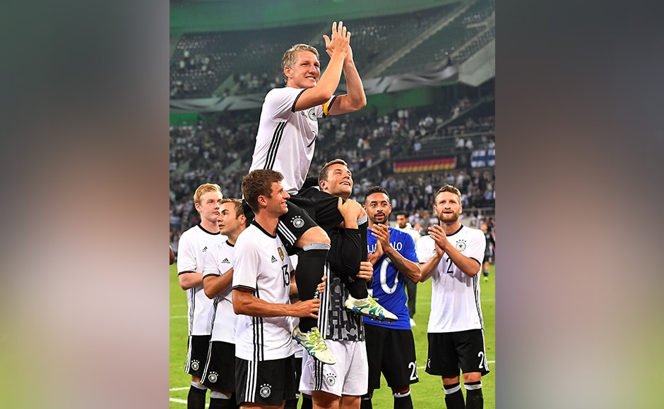 Germany's national team holding their captain Bastian Schweinsteiger one more time after he played his last match for the national team in Moenchengladbach, Germany, Wednesday, Aug. 31, 2016. Germany won the friendly soccer match against Finland with 2-0.AP