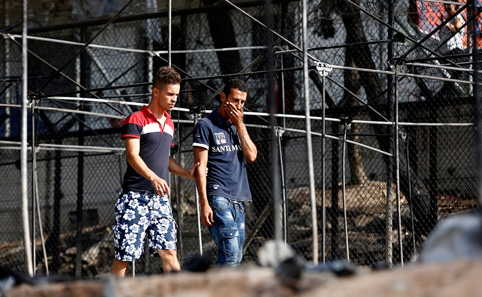 A migrant (R) reacts as he walks next to the remains of burned tents at the Moria migrant camp. Thousands have applied for asylum and the wait is long, ranging from weeks to months. Reuters