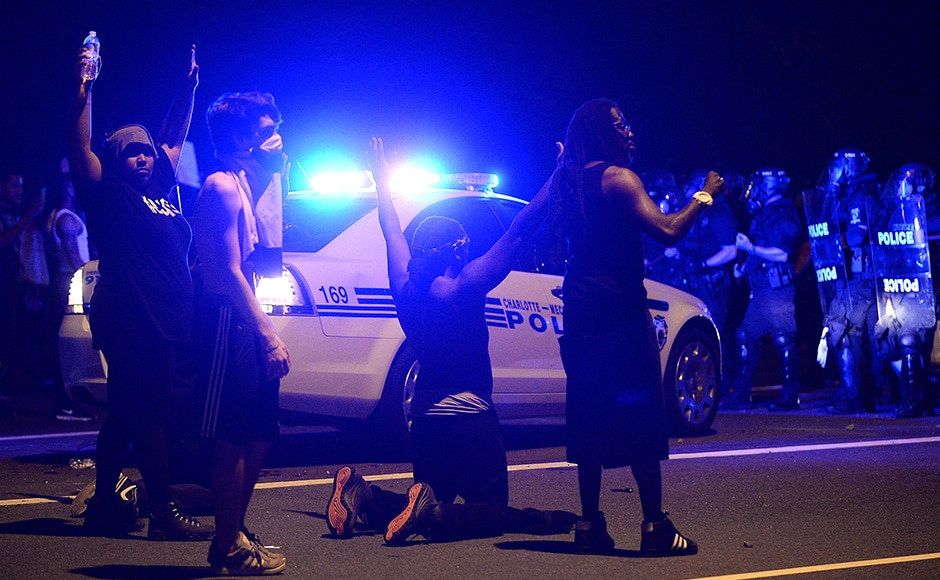 Protesters demonstrate in front of police. Authorities used tear gas to disperse protesters in an overnight demonstration that broke out Tuesday after Keith Lamont Scott was fatally shot by an officer at an apartment complex. AP