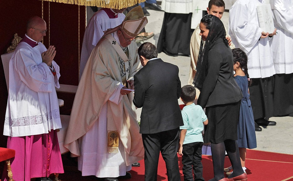 Brazilian mechanical engineer Marcilio Andrino, (left with back to camera) and his wife Fernanda Nascimento Rocha greet Pope Francis during the Canoninsation Mass at the Vatican on Sunday. Andrino's cure of a viral brain infection, declared a miracle by Pope Francis earlier this year, was the final step needed to declare Mother Teresa a saint. AP