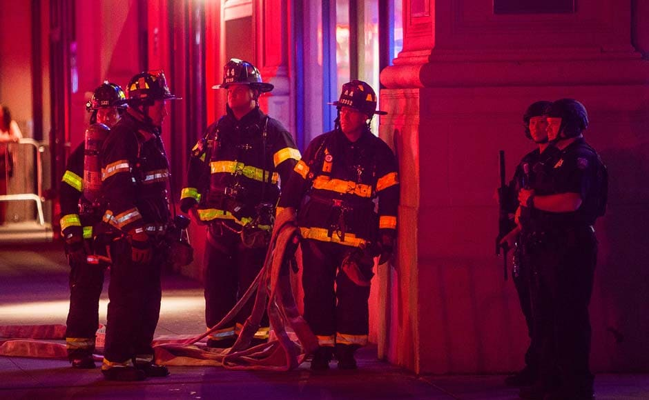 "Firefighters gather as heavily armed police block the area while they search for an explosive device on West 27th street and 7th Avenue in Manhattan, New York. An explosion in a crowded Chelsea neighborhood in Manhattan on Saturday night left more than two dozen people injured, and authorities called the blast an ""intentional act,"" but said there was no terrorist connection. New York Mayor Bill de Blasio also said a second site on 27th Street was being investigated. AP"