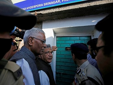 Sitaram Yechury and D Raja waiting out side the door of Syed Ali Shah Gellani in Srinagar on Sunday. PTI