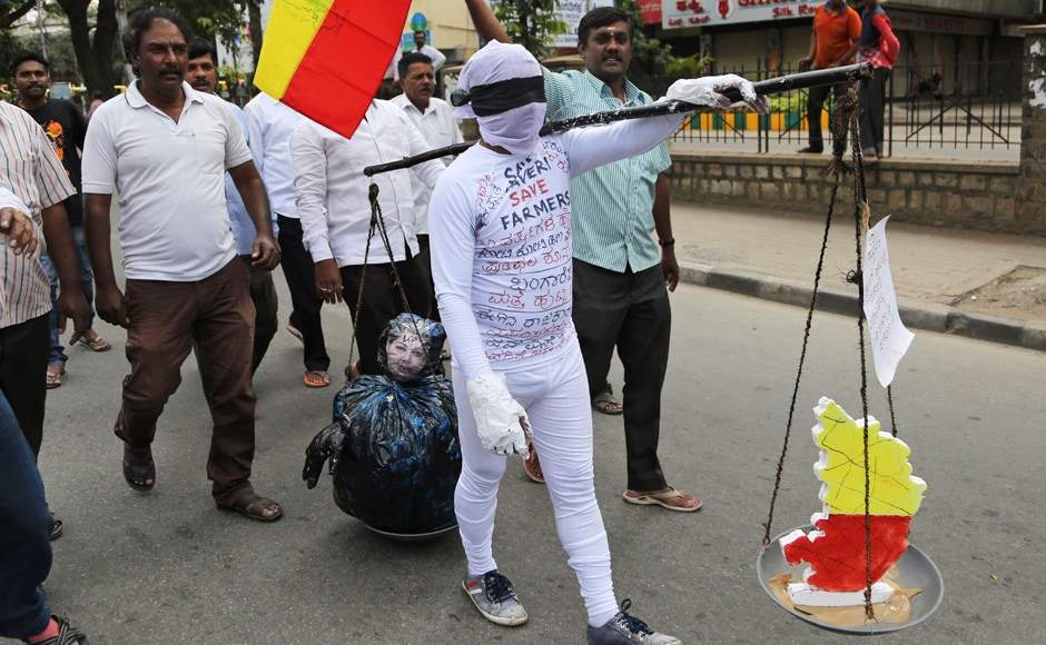 A supporter of a pro-Kannada organization carries a scale with an effigy of Tamil Nadu CM Jayalalithaa on one side and a map of Karnataka state on another, during a protest against a recent Supreme Court order on the Cauvery issue. Normal life was severely affected across Karnataka during the dawn-to-dusk strike. AP