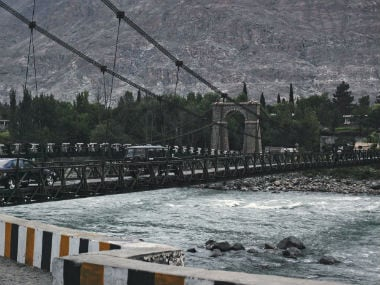 Vehicles cross a wooden plank cable suspension bridge over the Indus river. Reuters