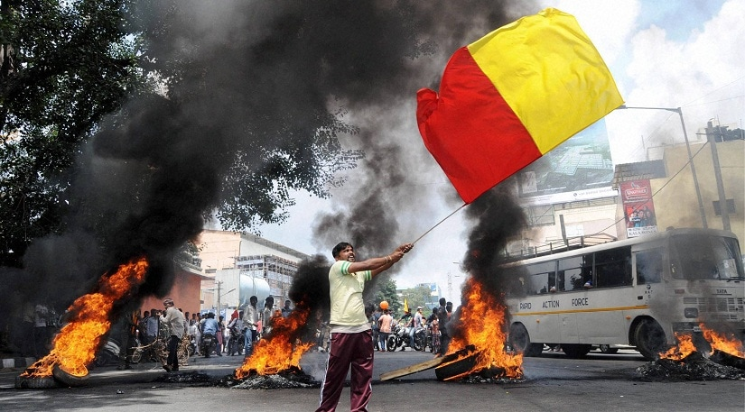Bengaluru : Pro-Kannada activists burn the tyres during Karnataka Bandh called in against the Supreme Court verdict on Cauvery water in Bengaluru on Friday. PTI Photo by Shailendra Bhojak (PTI9_9_2016_000097B)