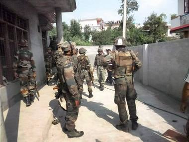Security personnel near the building where terrorists were hiding during an encounter at Allah Pir area in Poonch on Monday. PTI