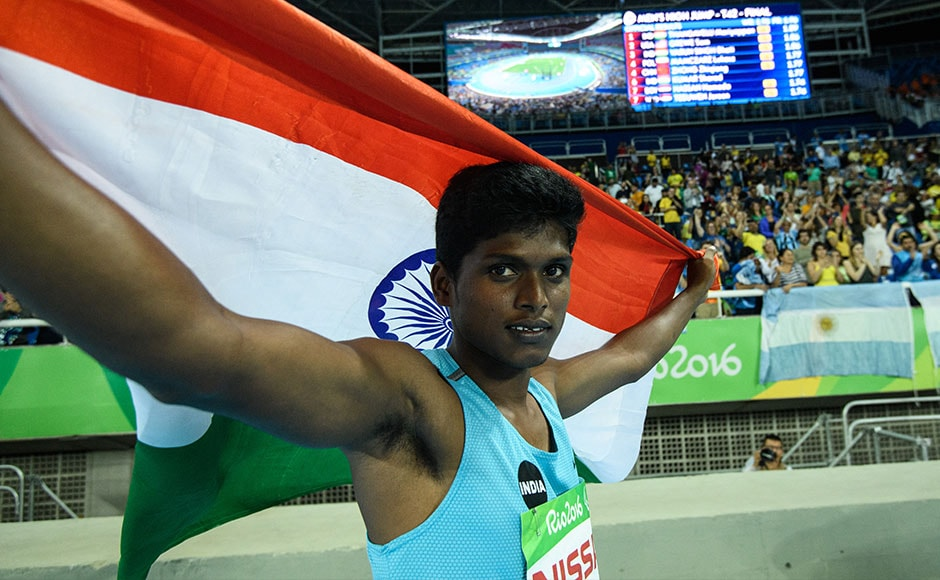 India's Mariyappan Thangavelu poses with the Indian flag after winning the gold medal in the men's final high jump. AFP