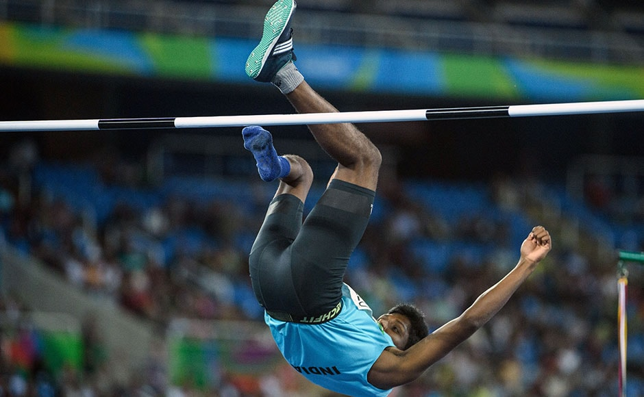 India's Mariyappan Thangavelu on the fall after a gold-medal winning jump in the men's high jump event. AFP