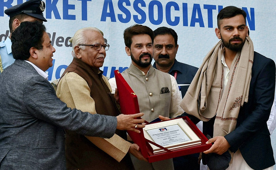 Uttar Pradesh Governor Ram Naik presents a memento to Indian cricket team captain, Virat Kohli to mark the 500th cricket test of the Indian team in Kanpur on Thursday. PTI Photo by Atul Yadav (PTI9_22_2016_000034B)