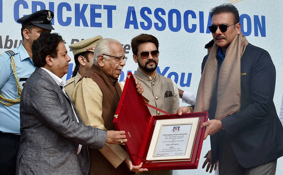 UP Governor Ram Naik and IPL Chairman Rajeev Shukla present a memento to former Indian Test captain Ravi Shastri, as BCCI President Anurag Thakur looks on, on the occasion of India's 500th Tests match at Green Park in Kanpur on Thursday. PTI Photo(PTI9_22_2016_000044B)