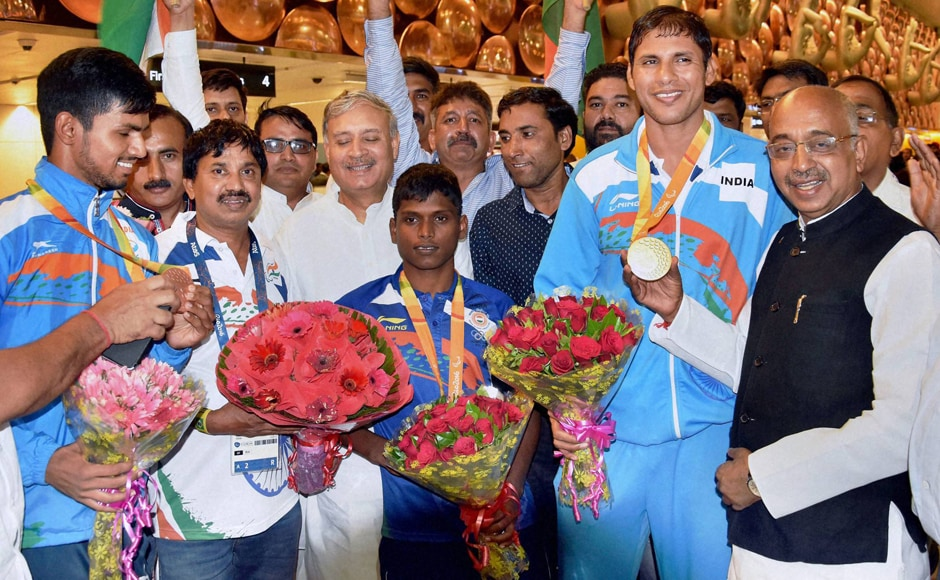 Sports minister Vijay Goel and MoS Rao Inderjit Singh greet Indian paralympians on their arrival at IGI airport in New Delhi on Thursday. PTI