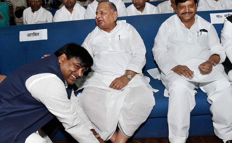 Much to the amusement of those present at the Raj Bhawan, a beaming Prajapati sat at the feet of SP supremo Mulayam Singh Yadav for photojournalists. (Photo: PTI)