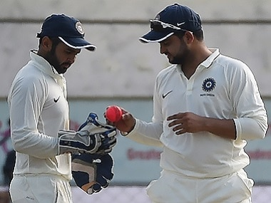India Green captain Suresh Raina and wicketkeeper Parthiv Patel discuss the pink ball during the Duleep Trophy cricket tournament. AFP