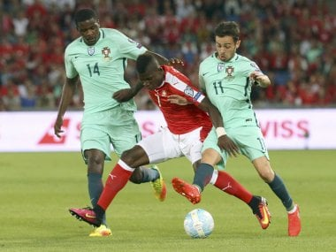 Switzerland's Breel Embolo fights for the ball from Portugal's William Carvalho and Bernardo Silva. Reuters
