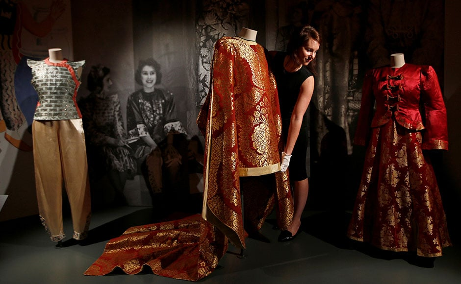 An exhibition featuring 90 years of the Queen's style opened at the Windsor Castle recently. A member of staff of the Royal Collection poses with pantomime outfits worn by Britain's Queen Elizabeth and Princess Margaret in the 1943 production of Aladdin. Reuters