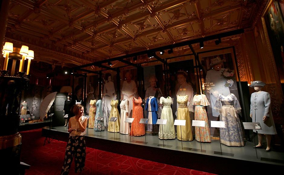 A member of staff of the Royal Collection looks at dresses worn by Britain's Queen Elizabeth, in the State Dining Room. Reuters